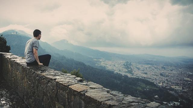 石垣の上に乗って遠くの街を見つめる1人の男性