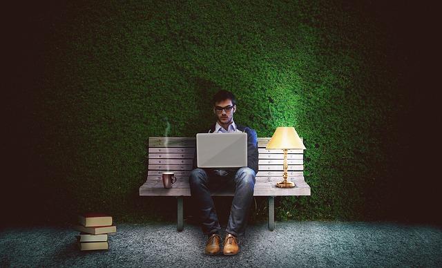 夜に公園のベンチでラップトップパソコンを持って作業している1人の男性