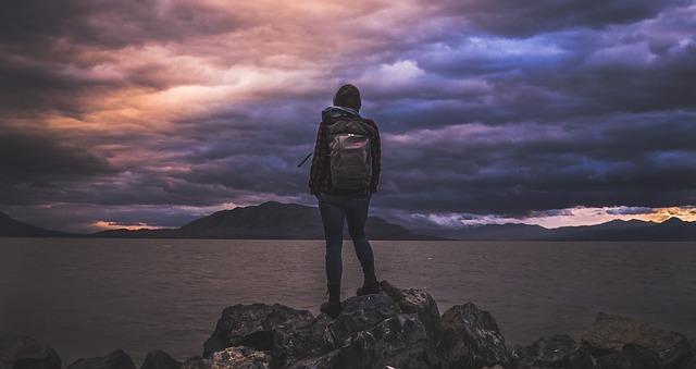 岩の上に立って対岸を眺める1人のバックパッカー