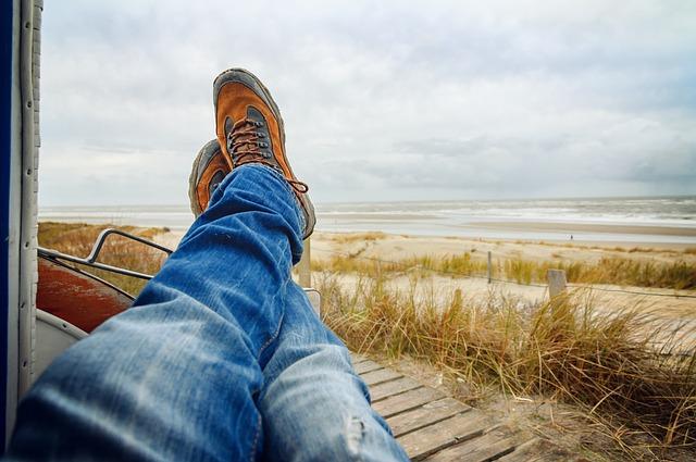海辺で足を組みながら寝転がる1人の男性