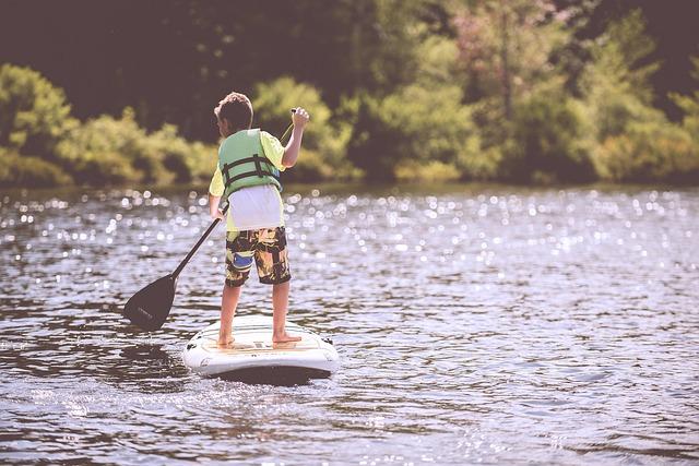 川をサーフボードで下る男の子