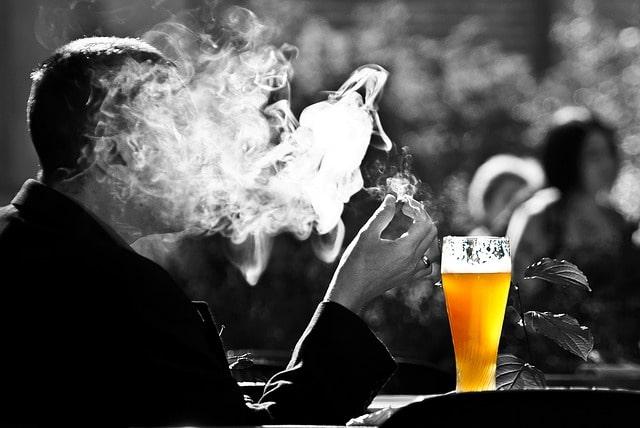 タバコを吸って煙に塗れる男