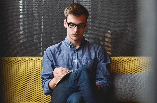 紙に書いている男性
