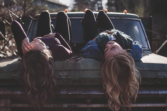 車に寝そべって楽しそうな女性二人