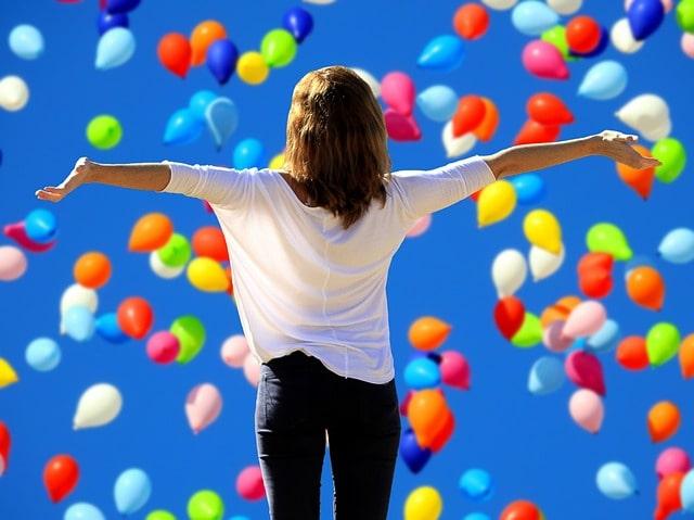 風船がいっぱいに広がる空の下で手を広げる少女