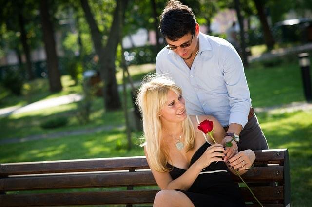 花束を女性に挿しだす男性