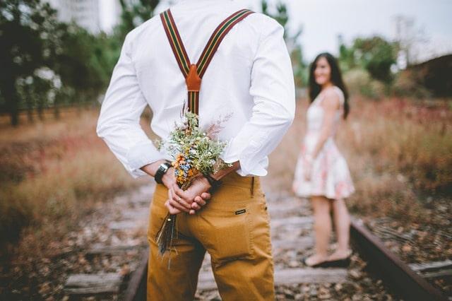 花束を隠し持って女性に渡そうとする男性