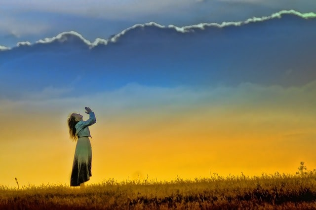 天に向かって手を合わせる人