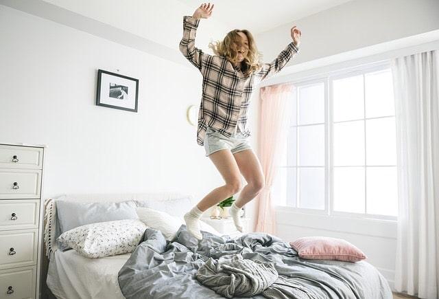 ベッドの上で飛び跳ねる女性