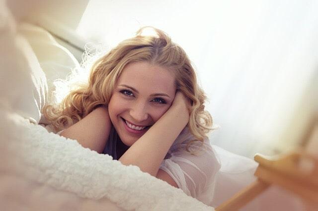 ベッドの上で嬉しそうな女性