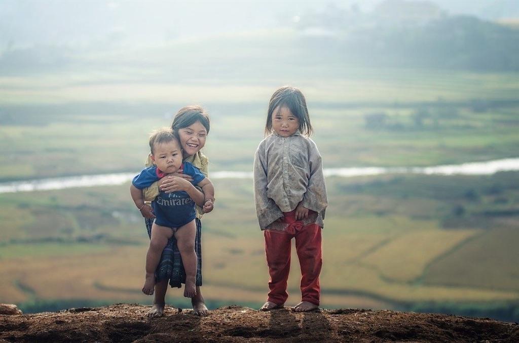 並んで立つ小さな女の子2人と男の子
