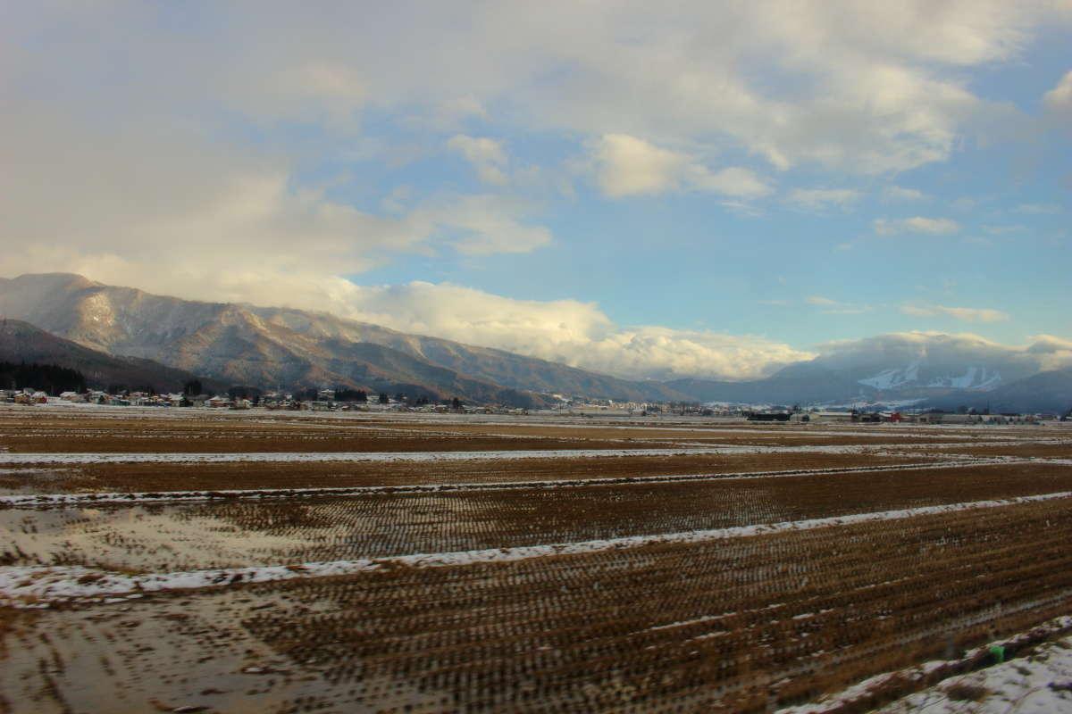 飯山盆地の向こうにスキー場が見えます