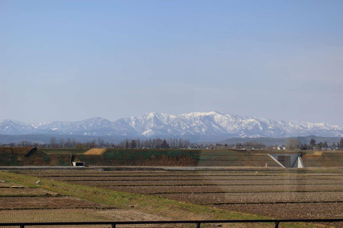 田園風景の向こうに雪をかぶった山並みを望む「フラワー長井線」の車窓