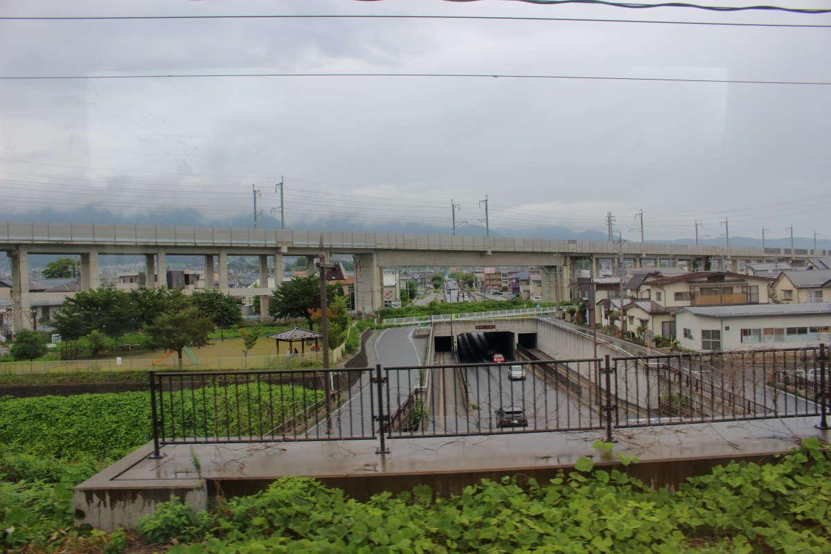 特急「ゆけむり」は北陸新幹線の高架をくぐり長野の市街地へ