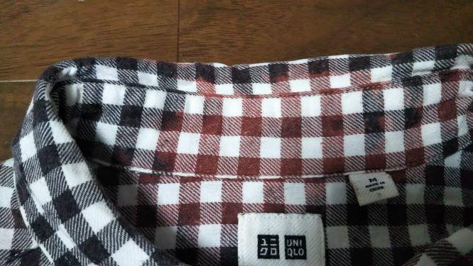 白黒のギンガムチェックのシャツが赤っぽく色落ちしている様子