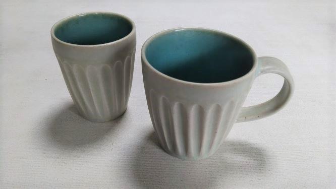 村山大介陶芸研究所のカップ2つ。内側にブルーの釉薬が塗られていて、外側は少しブルーが透けてグレーがかった白になっている。