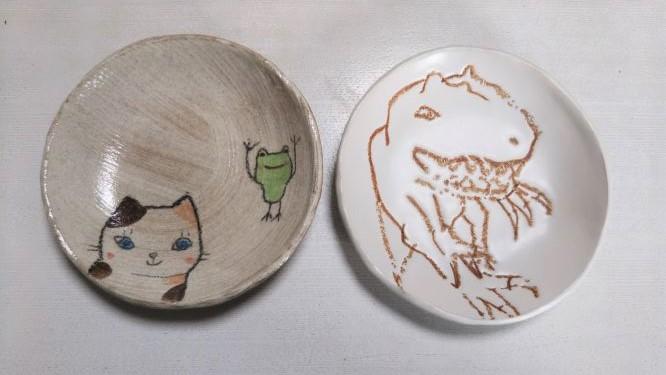 桜井ケンイチさんのお皿二枚の様子。猫と蛙が描かれたお皿と、ティラノサウルスのお皿。
