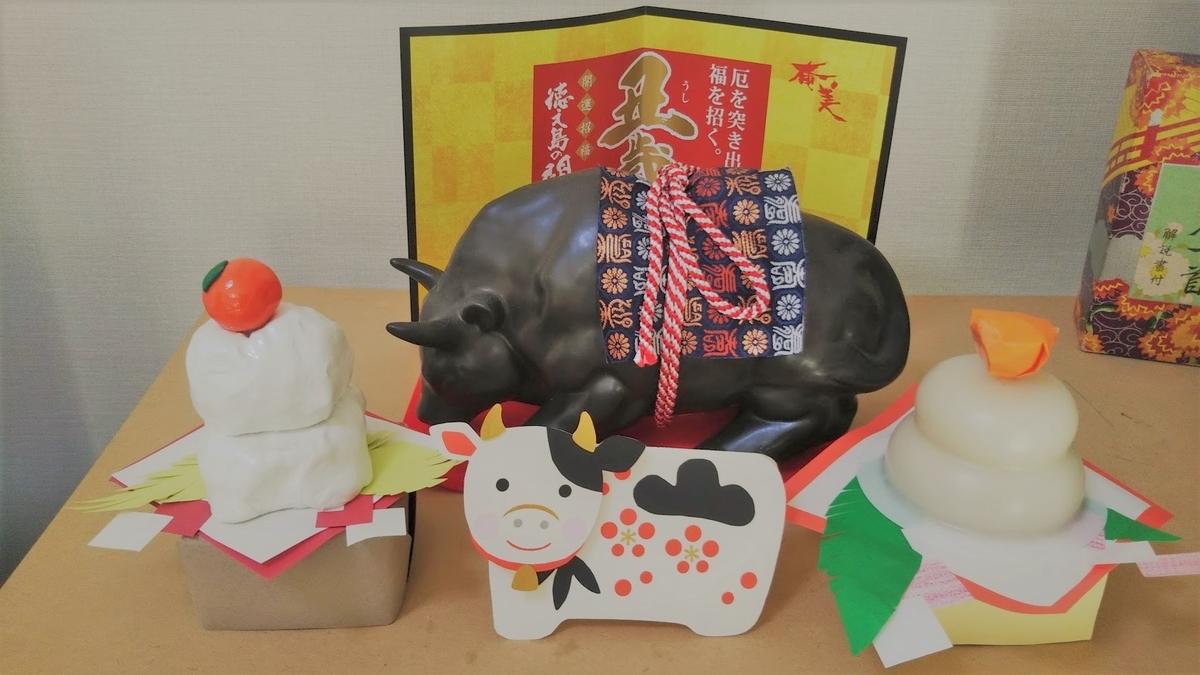正月飾りの様子。小さな鏡餅二つと牛型の焼酎瓶と牛のお年玉袋。