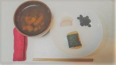 黒豆・かまぼこ・お餅のプレートと、シンプルな具のお雑煮の様子。