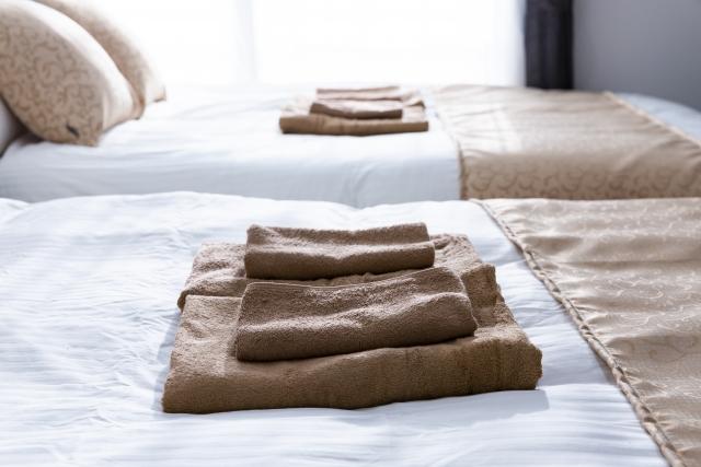 ベッドに置かれたタオル photo by photo AC