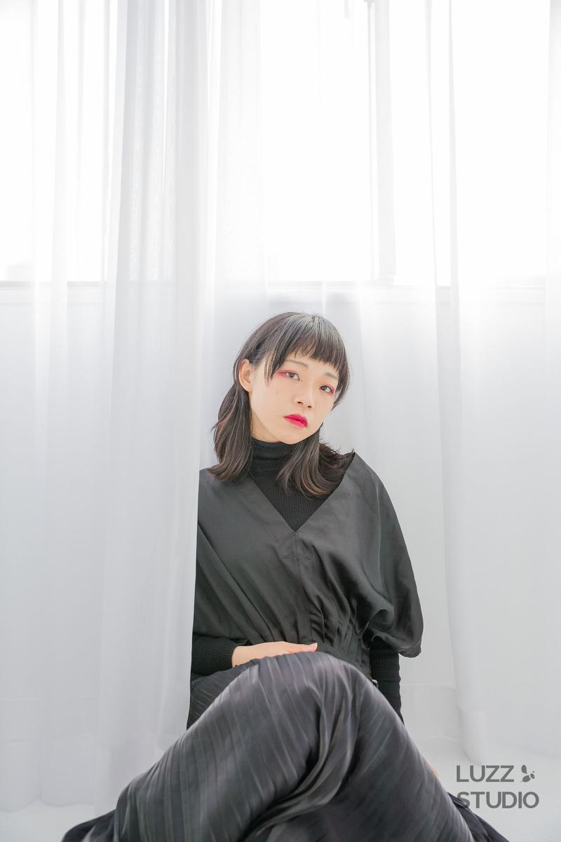 カーテンをバッグに座り込む女性の写真