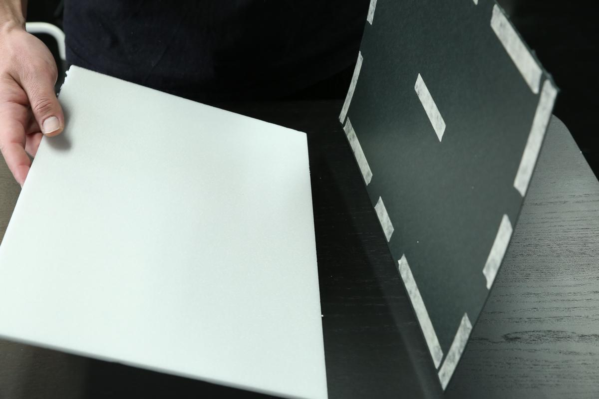カポック作りで黒のケント紙をホワイトボードに貼り付ける写真