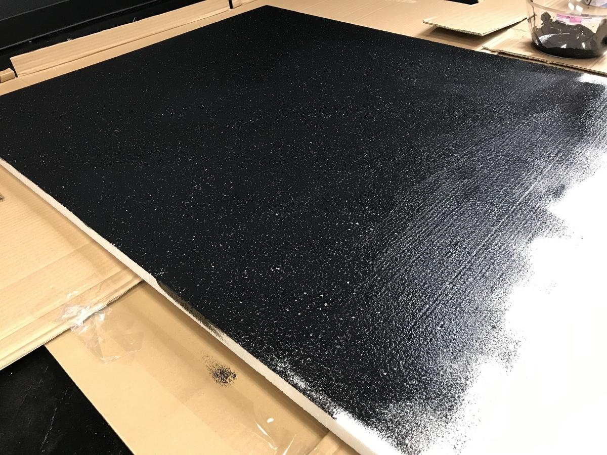 大きなカポックを作成する際の、黒の塗料を塗布している写真