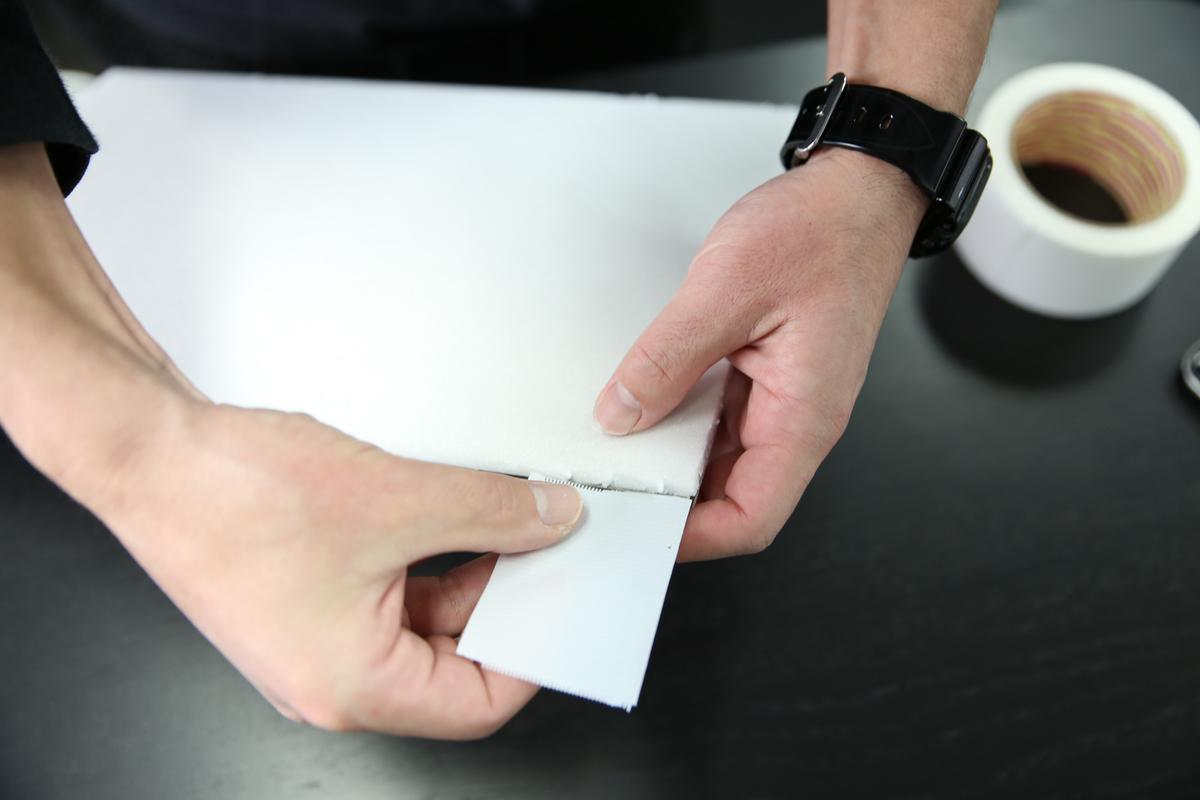 剥がした黒のテープの粘着部分に、白のテープを張り付けている写真