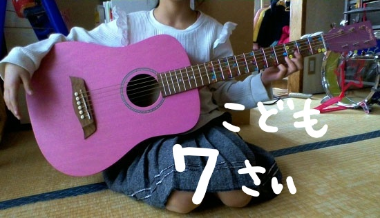 こどもが座って、ミニギターS.Yairi(エスヤイリ) YM-02を持っている。