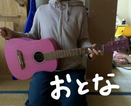 大人が座って、ミニギターS.Yairi(エスヤイリ) YM-02を持っている。
