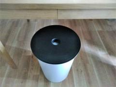 収納できる丸椅子。白い収納部の上に穴のあいた茶色い蓋。