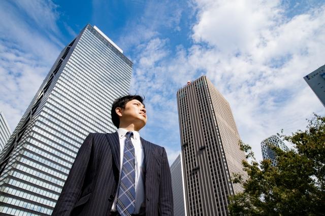 空を見上げるオフィス街のビジネスマン