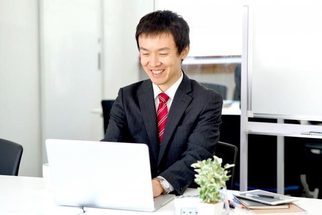 楽しそうにPCで仕事をするビジネスマン