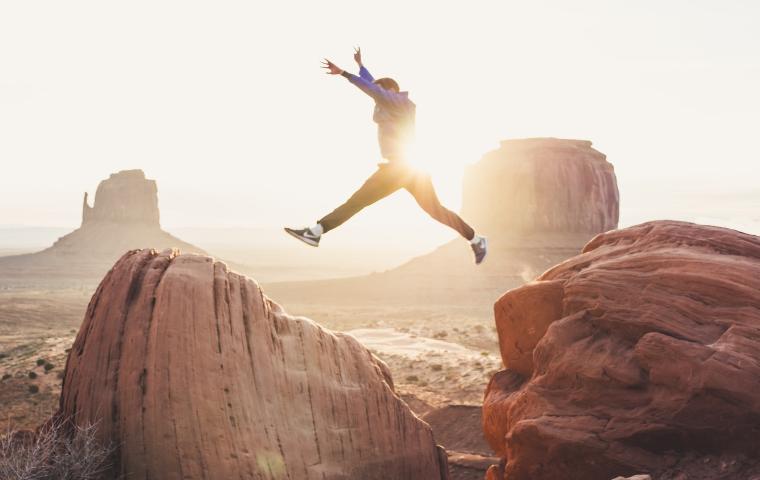 最高に楽しむ、岩場をジャンプする男性