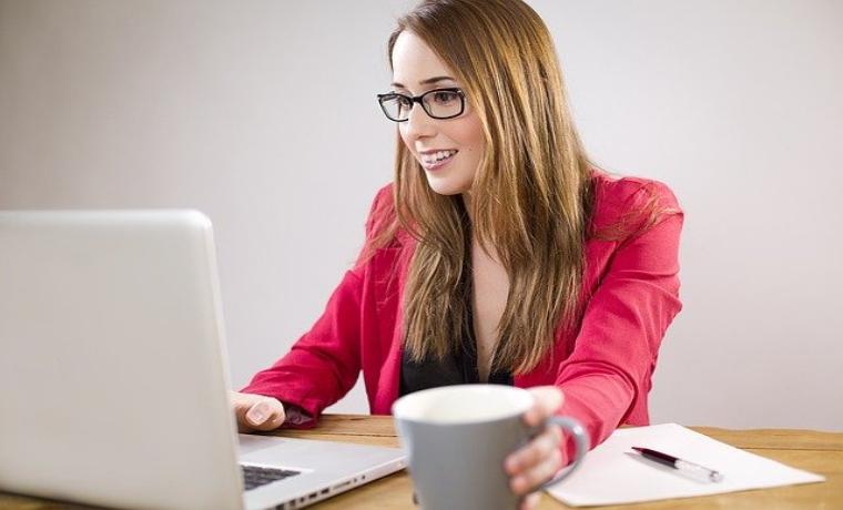 PCで仕事をする金髪のメガネをかけた女性
