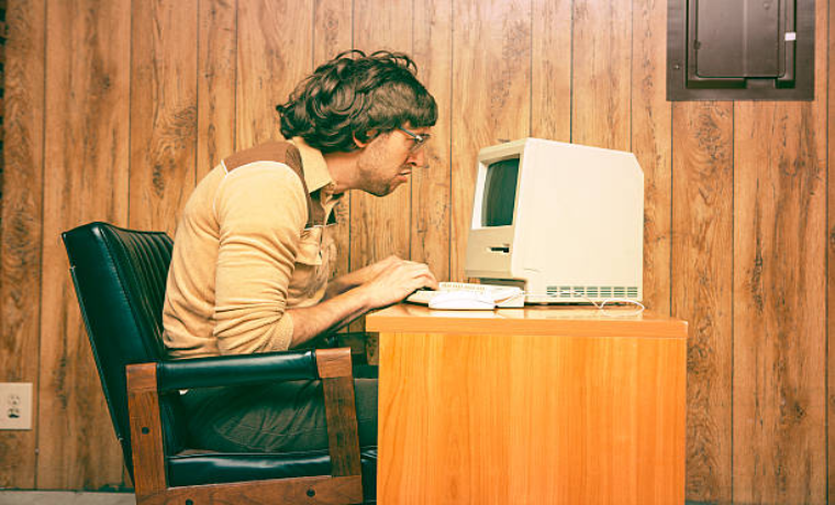 ショックを受けてパソコンを覗き込んでいるパーマの男性