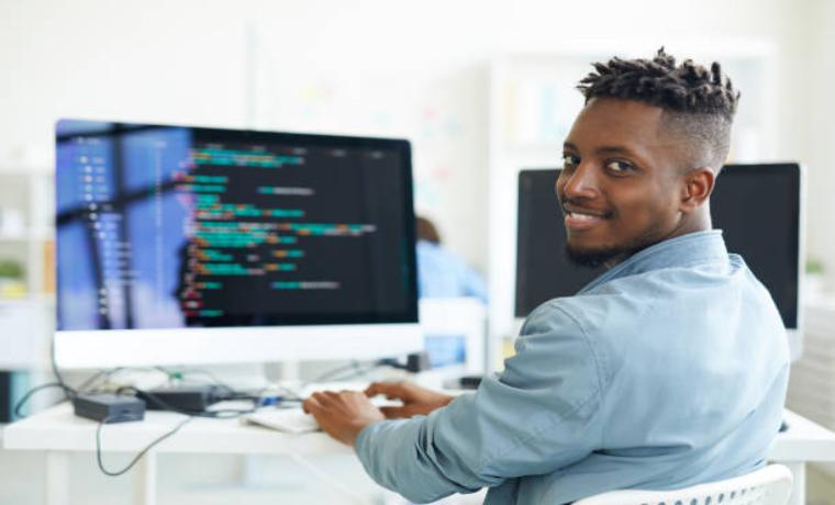 笑顔で振り向く若いプログラマーの黒人男性