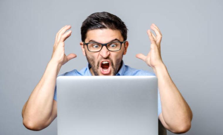 パソコンの前で慌ててショックを受けている男性