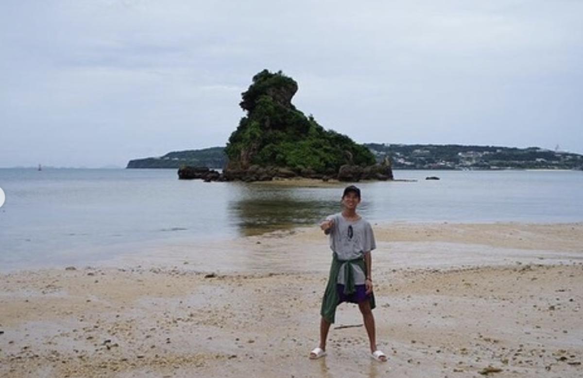 沖縄古宇利島でグッドポーズをするキャップを被った少年