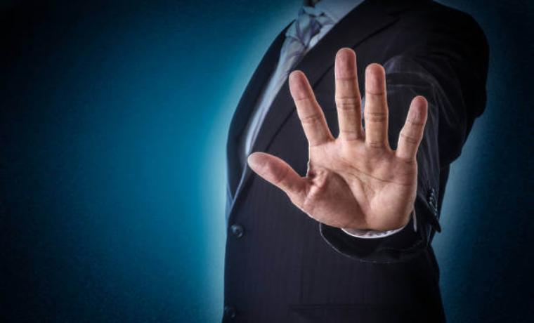 デメリットを伝えるスーツ姿の男性の手