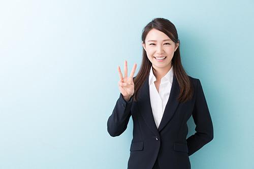 指で3をする女性