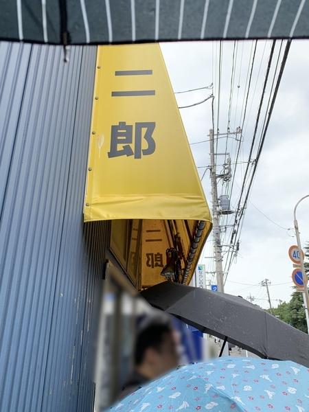 傘を差して開店を待つ