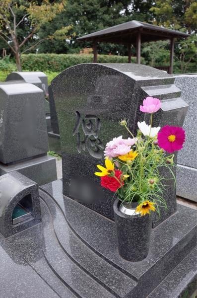 父の墓に花を供える