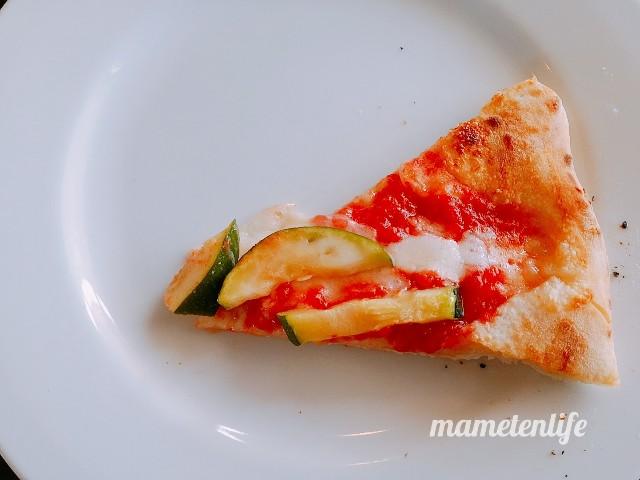 ラ・ポルタブルー(Pizzeria eBar LA PORTA BLU)のトマトソース、モッツアレラチーズとズッキーニとアンチョビのピッツアを一切れお皿に置いたところ