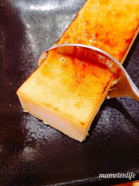 スシローのカタラーナアイスブリュレにスプーンをスプーンで切り分けているところ