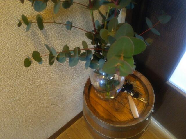 玄関の花台にしてユーカリを飾ったワインの樽画像