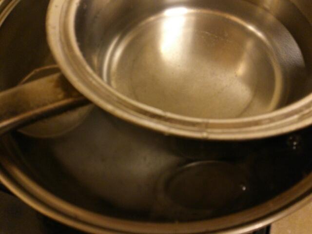 重曹を入れた大きな鍋で焦げ付いたステンレス鍋を煮ている画像