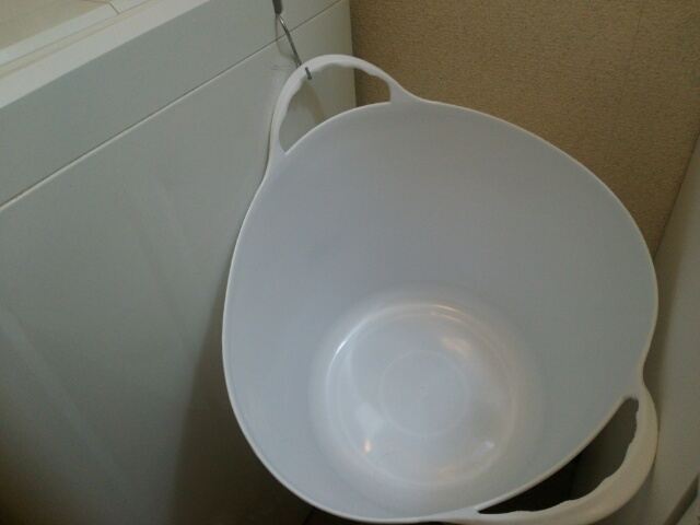 洗濯機に引っ掛けたKARUKOの白い洗濯かご