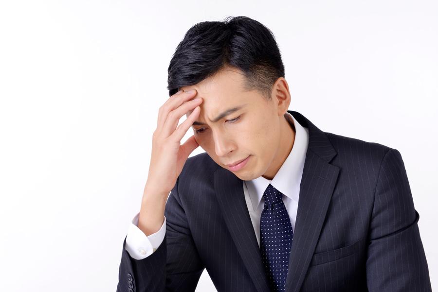 スーツ姿で右指5本を右目あたりに近づけて頭痛ともとれる表情の男性