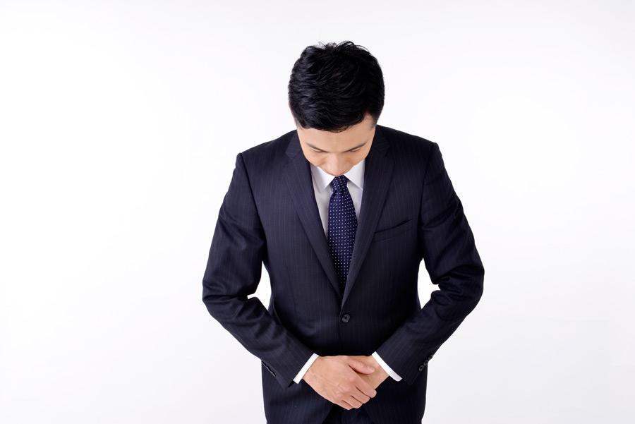 下っ腹を抑えて前屈みのスーツ着用の誠実そうなビジネスマン